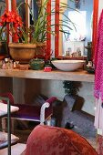 Wash basin, house plants and bottles of cosmetics on concrete counter in bathroom