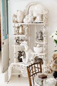 Collection of sculptures and teapots on white, vintage shelving