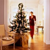 Decorated Christmas tree on trunk next to dish of biscuits on antique armchair in doorway and view of woman in grand living room