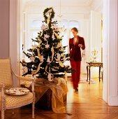 Geschmückter Weihnachtsbaum auf Truhe neben antikem Sessel mit Plätzchenschale im Durchgangsbereich und Blick auf Frau in herrschaftlichem Wohnzimmer