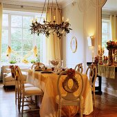 Festively set table below chandelier with lit candles in grand interior