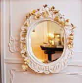 Reflexionen im Wandspiegel mit Blumendeko auf weißem geschnitzten Rahmen an weisser Wandverkleidung aus Holz
