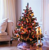 Gilt, floor-standing candlesticks in front of decorated Christmas tree in corner of room with traditional elements