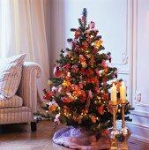 Goldene Bodenkerzenständer vor geschmücktem Weihnachtsbaum in Wohnzimmerecke mit traditionellem Flair