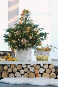 Christmas tree decorated with gold baubles and presents on shelf resting on stacked logs