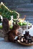 Squirrel figurine next to stacked pieces of chocolate in brass dish with Christmas decorations in background