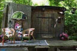 Wicker chairs on patterned rug in front of postcards pinned to old barn wall
