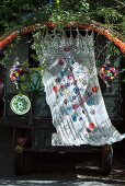 Wafting curtain with appliqué floral motifs and colourful crocheted trim decorating vehicle