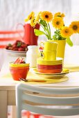 Colourful teacups and bowls on table in front of yellow flowers