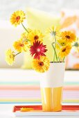 Gerbera daisies in white and yellow ceramic vase