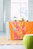 Printed tablecloth on table and convex stool in front of window