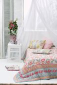 Floral bedspread on canopied bed