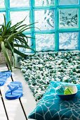 Green and white looped bathmat in front of turquoise glass brick wall