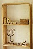Antiquarian books and vintage candlestick on rustic wooden shelving against whitewashed brick wall