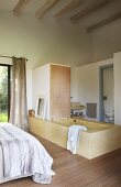 Free-standing bathtub in front of separate lavatory in simple bedroom