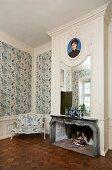 Spiegel und Portrait über dem Kamin in einem eleganten Raum mit blau-weiss gemusterter Tapete