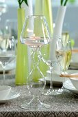 Lit tealight in glass candlestick in front of vases and wine glasses on table