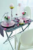 White plastic chairs around vintage folding table with place settings and decorations