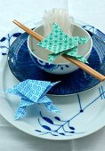 An Asian place setting with chopsticks and origami shapes
