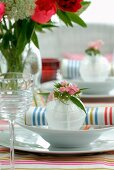 Place setting with flower arrangement and linen napkin with multicoloured stripes
