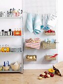 Crockery and drinks on metal kitchen shelving next to baskets and kitchen utensils hanging on perforated mounting panel