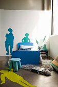 Blue stool in front of single bed with blue frame in corner of room and stencilled silhouettes of people on floor and wall
