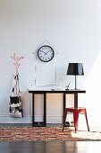 Red metal stool on rug in front of console table, black table lamp and wall clock