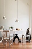 Pendant lamps with aluminium lampshades above set table with black and white curved bases and simple, printed chairs in minimalist period interior