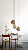 Red-painted kitchen chair at white table on wooden trestles and pendant lamps with spherical, basketwork shades made from natural materials