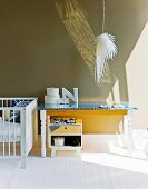 Wooden console table next to cot against mushroom grey wall and pendant lamp with white, feathery lampshade