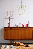 Fifties-style teak sideboard, table lamp and pendant lamp with wire frames and turned base and colourful rug in foreground