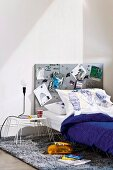 Teenager's bed and bedside table with metal frame and metal pinboard as headboard on flokati rug