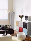 White, spherical plastic stool in front of half-height, locker-style, multicoloured metal cabinet and black designer sofa in corner of living room
