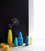 Yellow and blue bottles in front of flower drawn on black wall