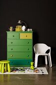 Green stool in front of green-painted chest of drawers next to white plastic chair against black wall