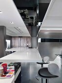 Modern, white kitchen counter and designer bar stools in an open living room