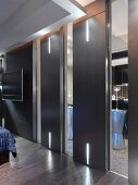 Designer bedroom with black sliding doors and integrated LED strip lighting in front of an en suite bathroom