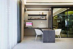 White shell chairs by a modern desk next to a glass wall