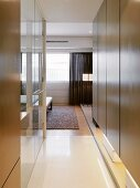 Hallway with modern built-in cupboards and view into an open bedroom