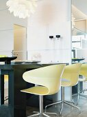 Modern mood - light colored swivel shell chairs by a table made of dark wood