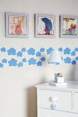 Detail of child's bedroom - table lamp on white chest of drawers against wall with framed pictures and applied pattern of clouds