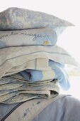 Stack of blue and white blankets and cushions