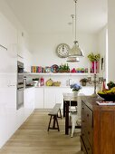 White built in kitchen with vintage dining table, bench and sideboard