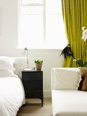 White bedroom with a chaise lounge and green curtain
