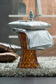 Cushion and throw with silver fabric covers on side table made from amber-coloured plastic and flokati rug