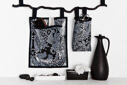 Black and white patterned storage bags hung on wall and black jug on white surface