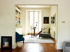 View through wide doorway into music room with music stand and instrument leaning against chaise longue next to balcony door