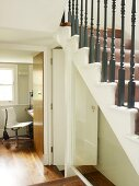 Staircase with turned, wooden balusters and view through open door of modern office swivel chair at workstation