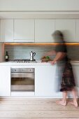 Modern kitchen - woman standing in front of kitchen units with white wall units and base units