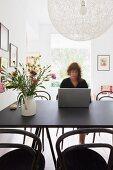 Frau arbeitet am Esstisch - Designer Hängelampe über schwarzem Tisch mit Blumenstrauss